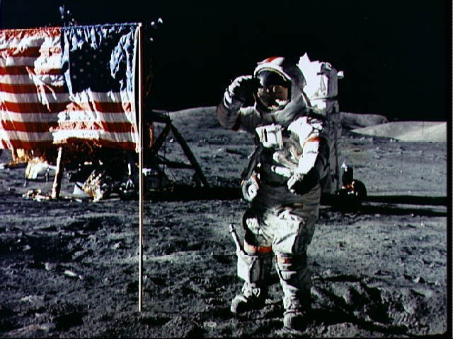 Astronaut Eugene Cernan salutes deployed U.S. flag on lunar surface